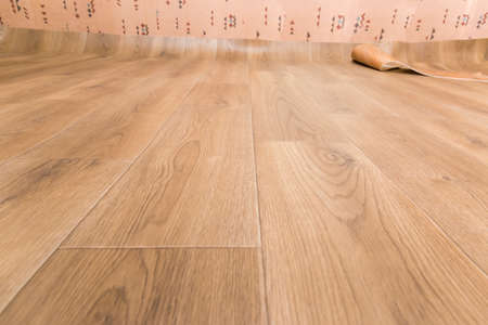 Sheet vinyl flooring with embossed imitation of wooden planks pattern during laying, fragment, low point view in selective focus