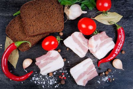 Slices of uncooked pork fatback with layers of lean meat among the some spices and vegetables, brown bread slices on a black surface, top view Banco de Imagens - 138529850
