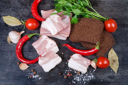 Partly sliced uncooked pork belly with layers of lean meat among the some spices and greens, chili, cherry tomatoes, brown bread, top view