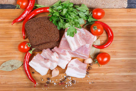 Partly sliced uncooked pork belly with layers of lean meat among the some spices, vegetables and greens, brown bread on the wooden cutting board, top view Banco de Imagens - 138529853
