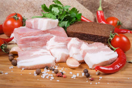 Partly sliced uncooked pork belly with layers of lean meat among the some spices, vegetables and greens, brown bread on the wooden surface, close-up in selective focus Banco de Imagens - 138530039