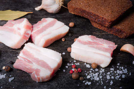 Slices of uncooked pork belly without of skin with layers of lean meat among the some spices and brown bread slices on a black surface close-up in selective focus Banco de Imagens - 138530046