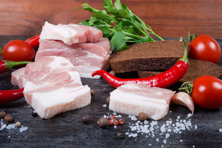 Partly sliced uncooked pork belly with layers of lean meat among the some spices and greens, chili, cherry tomatoes, brown bread, close-up in selective focus Banco de Imagens - 138530047