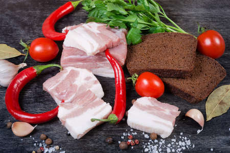 Slices of uncooked pork belly with layers of lean meat among the some spices and greens, chili, cherry tomatoes, brown bread slices on a black surface