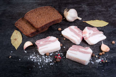 Slices of uncooked pork belly without of skin with layers of lean meat among the some spices and brown bread slices on a black surface Banco de Imagens - 138530051