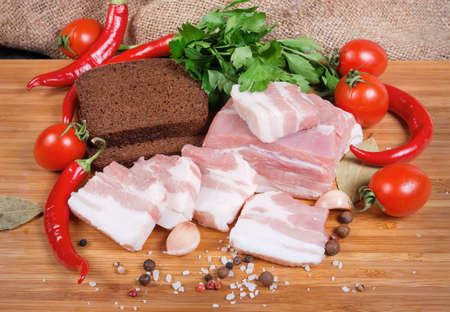 Partly sliced uncooked pork belly with layers of lean meat among the some spices and greens, chili, cherry tomatoes, brown bread on the wooden surface Banco de Imagens - 138530053