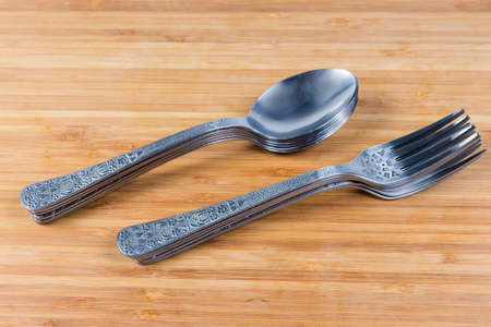 Stainless steel eating utensils consisting of spoons and forks stacked in two stacks on the wooden surface close-up  Stock fotó