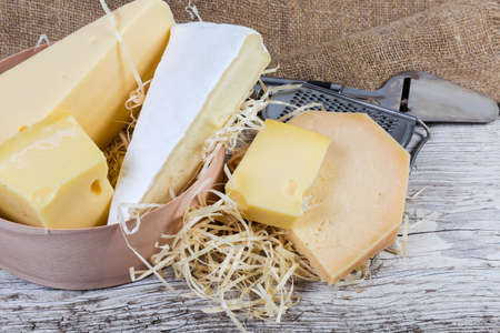 Pieces of different varieties of cheese in round wooden box and beside to her, againsr the cheese slicer and grater on the old wooden surface with burlap    Stock fotó