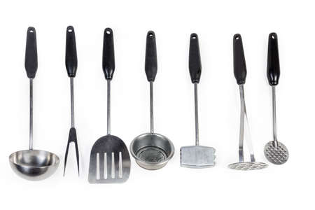 Set of stainless steel cooking utensils with plastic handles for various purposes laid out on a white background