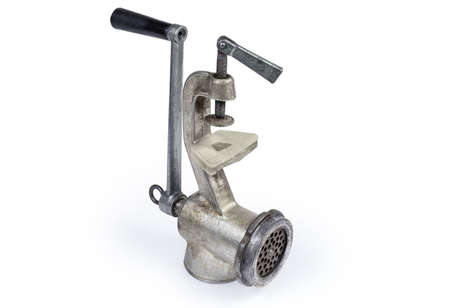 Inverted old hand-powered meat grinder assembled for use standing on a white background
