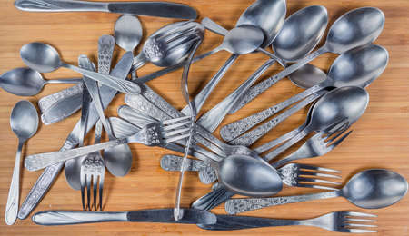 Various stainless steel eating utensils - spoons, forks, table knives and tea spoons scattered on the wooden surface, top view, background