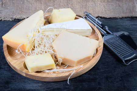 Pieces of different varieties of cheese on the wooden serving board, cheese slicer and grater on a black surface   Stock fotó