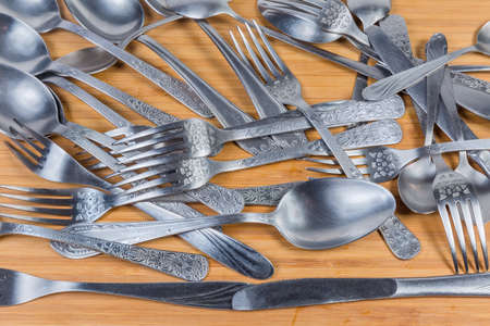 Various stainless steel eating utensils - spoons, forks, table knives and tea spoons scattered on the wooden surface, fragment, background