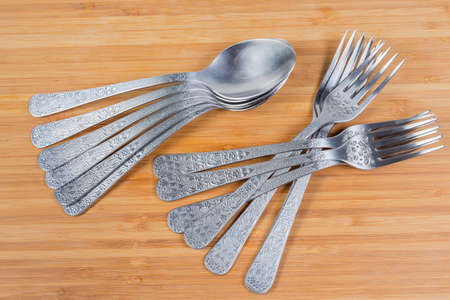 Stainless steel eating utensils consisting of spoons and forks on the wooden surface, top view  Stock fotó