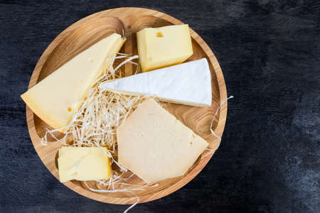 Pieces of different varieties of cheese on the wooden serving board located left on a black surface, top view  Stock fotó