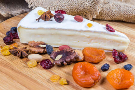 Piece of brie cheese in the form of a sector among the several different nuts and dried fruits on the wooden surface, close-up in selective focus