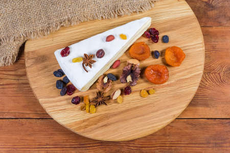 Piece of brie cheese in the form of a sector among the several different nuts and dried fruits on the round wooden cutting board on the rustic table, top view
