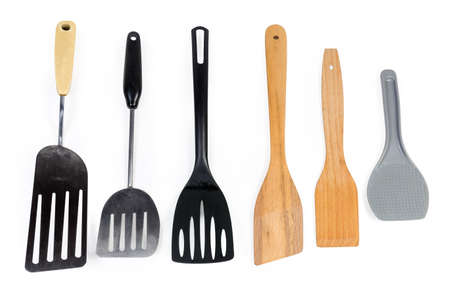 Different kitchen spatulas made with stainless steel, wooden and plastic  and laid out on a white background