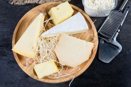 Pieces of different varieties of cheese on the wooden serving board, cottage cheese, cheese slicer and grater on a black surface, top view