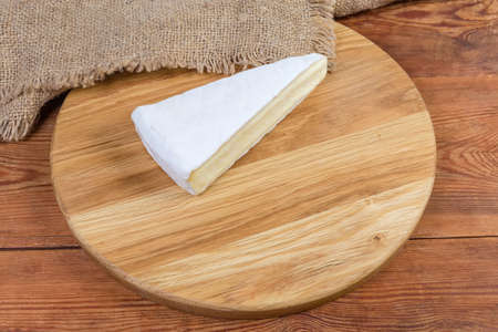 Piece of brie cheese in the form of a sector on the round wooden cutting board on the rustic table  Stock fotó
