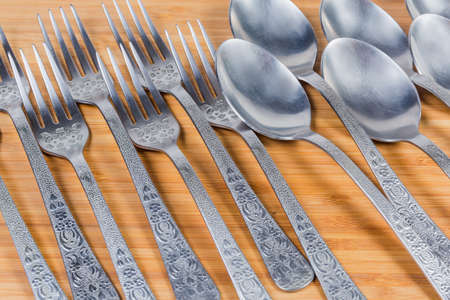 Stainless steel eating utensils consisting of spoons and forks laid out on the wooden surface, fragment close-up in selective focus