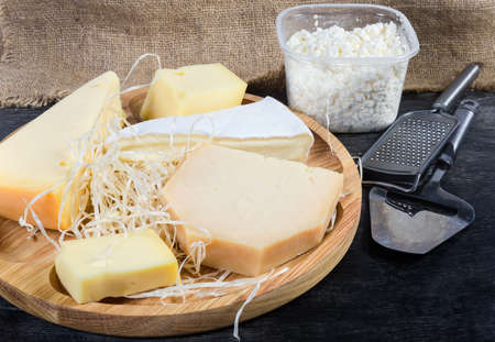 Pieces of different varieties of cheese on the wooden serving board against the cottage cheese and cheese slicer and grater