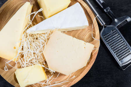 Pieces of different varieties of cheese on the wooden serving board, cheese slicer and grater on a black surface, top view Reklamní fotografie