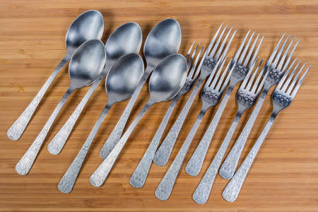 Stainless steel eating utensils consisting of spoons and forks laid out on the wooden surface, top view