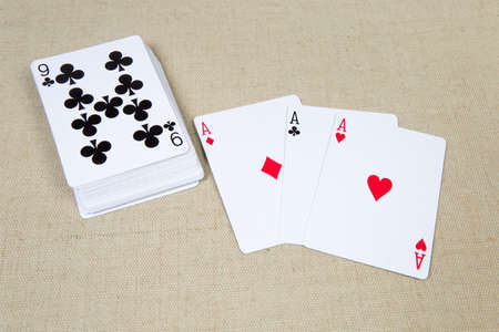 Three French playing cards ace clubs, diamonds and hearts and deck cards face-up beside on the cloth surface