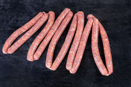 Uncooked thin long pork sausages for grilling with herbs in natural casing on the black surface, top view