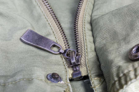 Slider of metal zipper fastener with metal puller on a fragment of jacket olive color close-up in selective focus