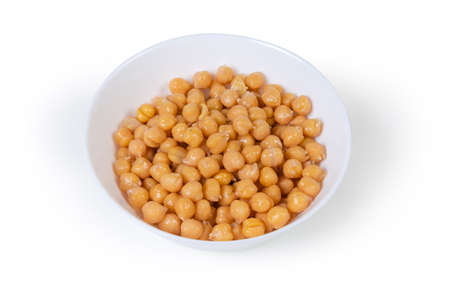 Boiled whole slightly sprouted yellow chickpeas in the white bowl on a white background  写真素材