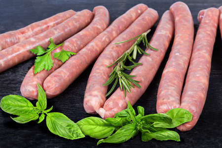Uncooked thin long pork sausages for grilling in natural casing, some fresh herbs on the black surface, fragment close-up in selective focus 스톡 콘텐츠 - 139277744