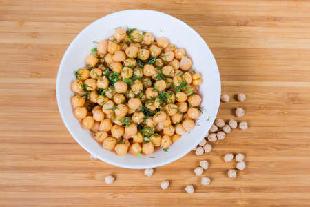 Boiled whole yellow chickpeas sprinkled with chopped dill in the white bowl on the wooden surface with the same uncooked dried chickpeas, top view
