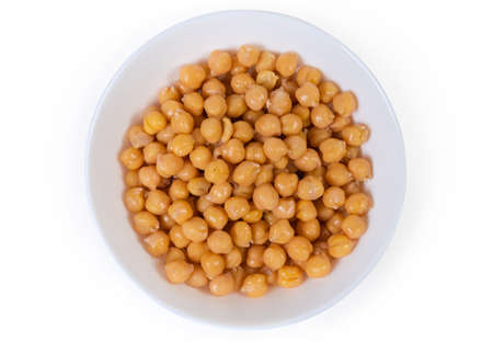 Boiled whole yellow chickpeas in the white bowl on a white background, top view