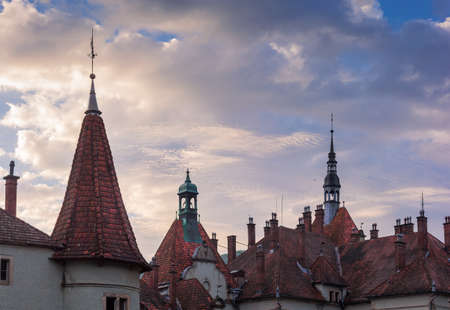 Tile roof of the old castle 19th century with towers, belfry and chimneys against the morning sky with clouds, fragment. Zakarpattia Oblast, Ukraine   스톡 콘텐츠