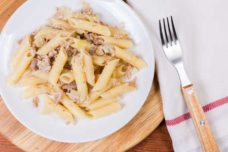 Boiled penne pasta mixed with stuffing of stewed minced pork and fried onion in navy-style on dish, fork on cloth napkin, fragment top view