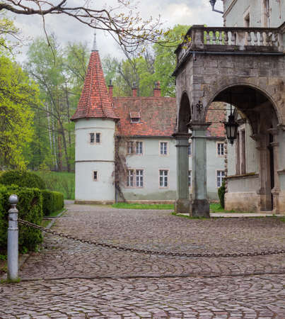 Fragment of the old castle 19th century with portico and round tower in early spring cloudy morning. Zakarpatska Oblast, Ukraine   스톡 콘텐츠