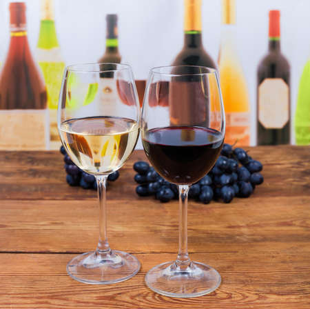 Glass of red wine and glass of white wine standing on the old rustic table on a blurred background of bottles in selective focus