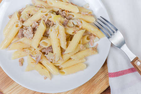 Boiled penne pasta mixed with stuffing of stewed minced meat and fried onion in navy-style on white dish with fork, fragment top view