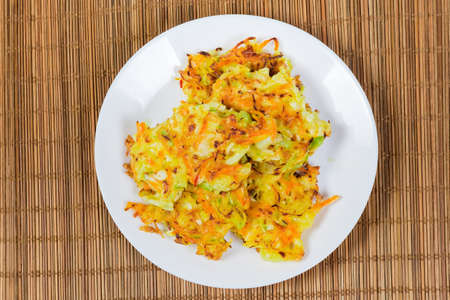 Fried savory cabbage pancakes on white dish on the bamboo table mat, top view Archivio Fotografico - 142425288