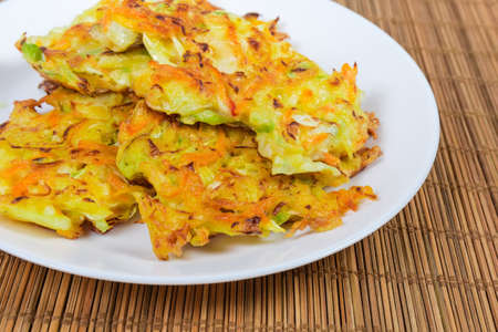 Fried savory cabbage pancakes on white dish on the bamboo table mat, fragment close-up in selective focus Archivio Fotografico - 140348522