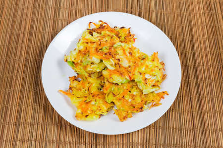 Fried savory cabbage pancakes on white dish on the bamboo table mat