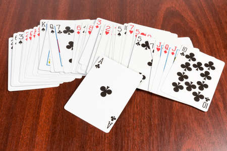 Deck of french playing cards with standard English pattern scattered face-up and ace of clubs on top on the wooden table