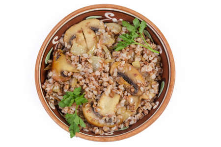 Freshly prepared buckwheat porridge with fried chopped mushrooms and onions in the clay glazed dish on a white background, top view Reklamní fotografie
