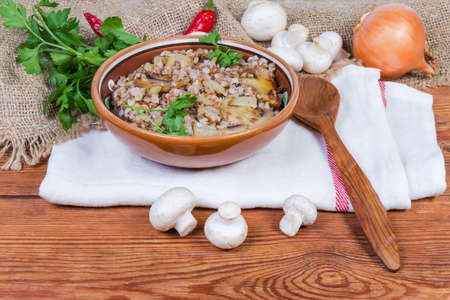 Buckwheat porridge with fried mushrooms and onions in the clay dish, wooden spoon on napkin among the some raw ingredients on the rustic table