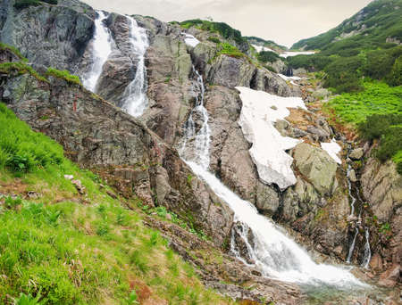Waterfall with several water flows on a mountain river, bottom view. Tatra Mountains