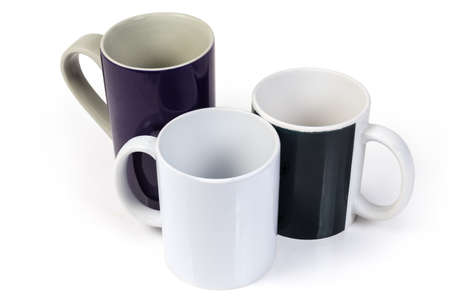 Three empty ceramic cups different sizes white, black and navy blue colors with handles on a white backgrounde Imagens