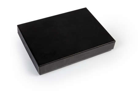Small black flat rectangular cardboard box with closed lid on a white background