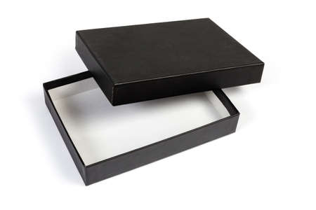 Small black flat rectangular cardboard box with partly open lid on a white background 스톡 콘텐츠